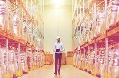 Homem de negócios feliz com a prancheta no armazém Imagem de Stock