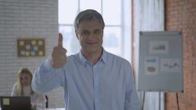 Homem de negócios feliz Image nos polegares do escritório acima do sorriso e de apontar com dedo 4K filme