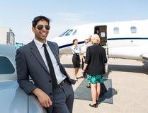 Homem de negócios feliz Leaning On Car no aeroporto Fotografia de Stock