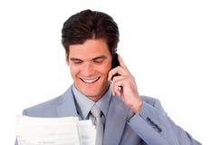 Homem de negócios feliz no telefone que prende um jornal Foto de Stock Royalty Free