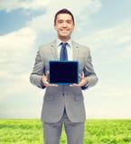 Homem de negócios feliz no terno que mostra a tela do PC da tabuleta Imagem de Stock