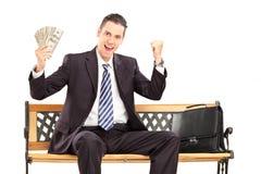 Homem de negócios feliz no terno que senta-se em um banco e que guarda o dinheiro Imagens de Stock Royalty Free