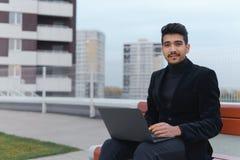 Homem de negócios feliz no trabalho no portátil que senta-se fora e nos olhares afastado à câmera Fotografia de Stock Royalty Free