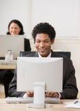 Homem de negócios feliz nos auriculares que trabalham no computador Fotografia de Stock Royalty Free