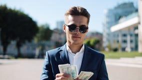 Homem de negócios feliz novo nos óculos de sol e um terno que conta o dinheiro e que anda na rua Ele que selebrating o seu bem su video estoque