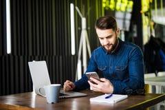 Homem de negócios feliz novo que sorri ao ler seu smartphone Retrato da mensagem de sorriso da leitura do homem de negócio com sm Imagem de Stock Royalty Free