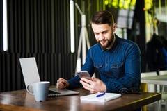 Homem de negócios feliz novo que sorri ao ler seu smartphone Retrato da mensagem de sorriso da leitura do homem de negócio com sm Fotografia de Stock