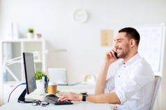 Homem de negócios feliz que chama o smartphone no escritório imagens de stock