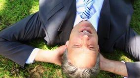 Homem de negócios feliz que encontra-se na grama filme