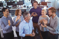 Homem de negócios feliz que está pelos colegas que aplaudem imagens de stock royalty free