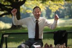Homem de negócios feliz que joga a xadrez Fotografia de Stock