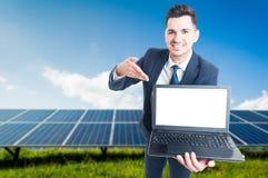 Homem de negócios feliz que mostra o portátil com tela vazia Foto de Stock Royalty Free