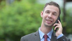 Homem de negócios feliz que pensa ao falar no telefone fora filme