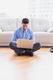 Homem de negócios feliz que senta-se no assoalho usando seu portátil Foto de Stock Royalty Free