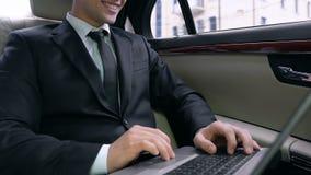 Homem de negócios feliz que senta-se no carro, usando o portátil e sorrindo, negócio bem sucedido video estoque