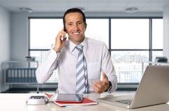 Homem de negócios feliz que trabalha no portátil do computador que fala no telefone celular no escritório Fotografia de Stock Royalty Free