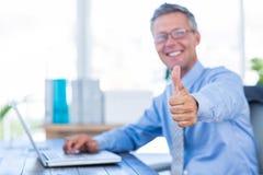 Homem de negócios feliz que usa o laptop e olhando a câmera com polegares acima Foto de Stock