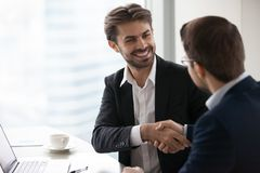 Homem de negócios feliz satisfeito no sócio comercial do aperto de mão do terno que faz o negócio foto de stock royalty free