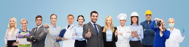 Homem de negócios feliz sobre trabalhadores profissionais fotos de stock royalty free