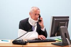 Homem de negócios ferido em sua mesa no telefone fotos de stock