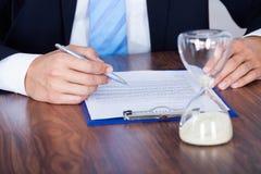 Homem de negócios Filling Form In Front Of Hourglass fotos de stock royalty free