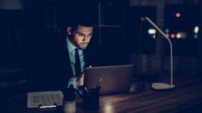 Homem de negócios focalizado Working Laptop Office na noite foto de stock