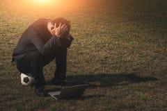 Homem de negócios forçado com cabeça nas mãos no campo de futebol, homem de negócios novo forçado que senta-se fora do escritório imagem de stock