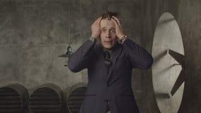 Homem de negócios forçado com cabeça nas mãos no desespero video estoque