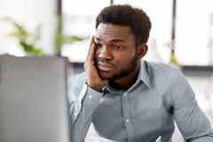 Homem de negócios forçado com o computador no escritório imagem de stock