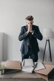 Homem de negócios forçado com os originais e os dobradores que estão na tabela no escritório Foto de Stock Royalty Free