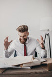 Homem de negócios forçado com os originais e os dobradores que sentam-se na tabela no escritório Foto de Stock