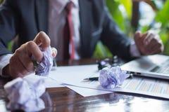 Homem de negócios forçado com os papéis e as cartas que sentam-se na tabela dentro Fotografia de Stock