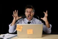 Homem de negócios forçado louco novo que grita o trabalho desesperado no esforço com laptop foto de stock