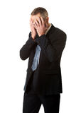 Homem de negócios forçado que cobre sua cara com as mãos Fotografia de Stock Royalty Free