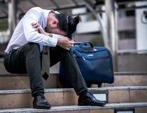 Homem de negócios forçado que senta-se na escadaria exterior Assento falido do homem de negócios exterior fotos de stock