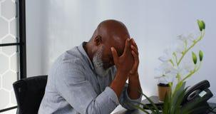 Homem de negócios forçado que senta-se na mesa com mão na testa 4k filme