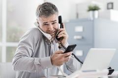 Homem de negócios forçado que tem chamadas do múltiplo imagens de stock
