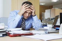 Homem de negócios frustrante At Office Desk fotografia de stock royalty free