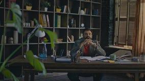 Homem de negócios frustrante que põe a cabeça sobre a mesa no escritório domiciliário Homem de negócios Tired filme