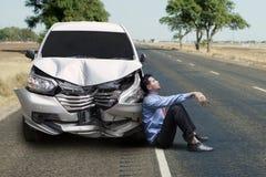 Homem de negócios frustrante que senta-se perto de um carro quebrado fotos de stock