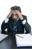 Homem de negócios frustrante, virado em sua mesa Fotografia de Stock Royalty Free