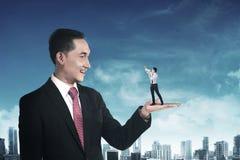 Homem de negócios gigante que guarda o homem pequeno que grita com megafone Imagens de Stock