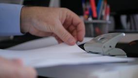 Homem de negócios Hands no escritório que faz furos nos documentos para o arquivo fotografia de stock