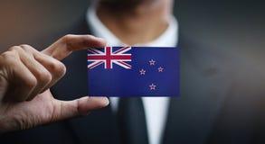 Homem de negócios Holding Card da bandeira de Nova Zelândia foto de stock royalty free