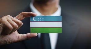 Homem de negócios Holding Card da bandeira de Usbequistão foto de stock royalty free