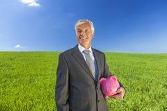 Homem de negócios Holding Piggy Bank do homem no campo fotos de stock royalty free