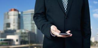 Homem de negócios Holding Smartphone à disposição com cidade do negócio e construções incorporadas no fundo imagens de stock royalty free