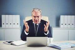 Homem de negócios idoso irritado que fala no bate-papo video fotografia de stock