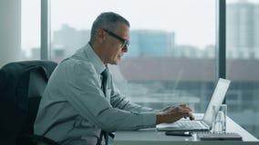 Homem de negócios idoso que trabalha com o computador no escritório moderno o seu para trás é os danos video estoque