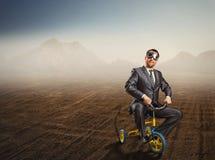 Homem de negócios impar que monta uma bicicleta pequena fotos de stock royalty free